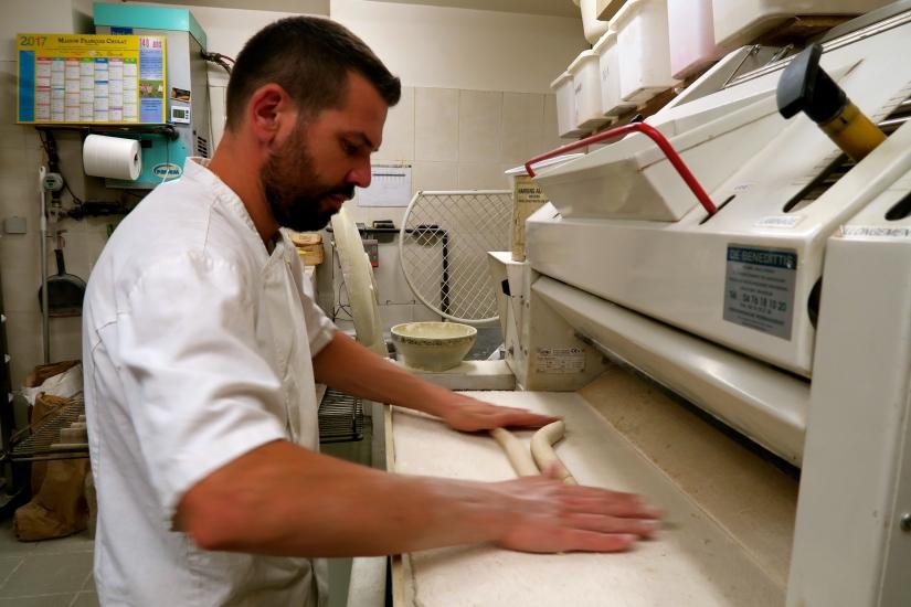 Il met les morceaux un à un dans la façonneuse qui éjecte des pâtes en forme de baguettes.