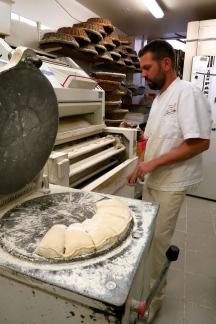 Ensuite, Nicolas insère des gros morceaux dans le diviseur, qui sépare la pâte en des morceaux de taille égale.